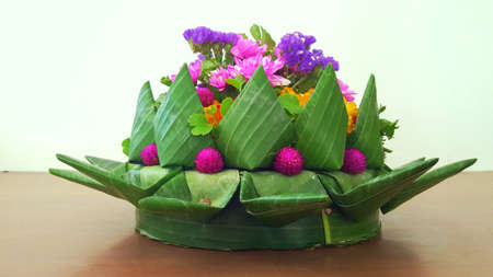 A photo of giant Krathong art work at the Loy Krathong Festival day of Thailand, made of green banana leaves and flowers (Chrysanthemum, Marigold, etc) on wood table, close up