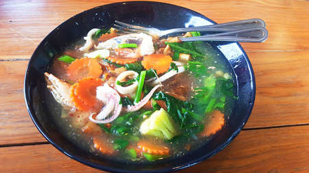 Asia - Asian eating food, Thai food, a Noodles in Thick Gravy with Seafood (Rad Na Ta Lay), close up