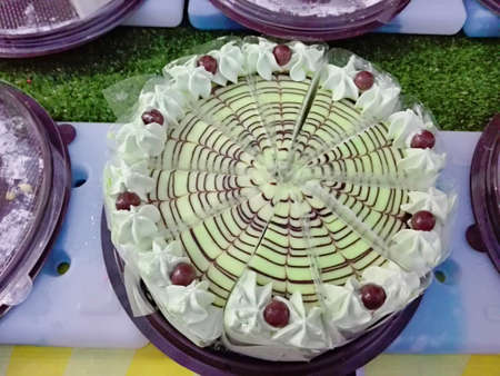 A photo of colorful vanilla cream cake decorated with topping at streed food market of thailand, close up 版權商用圖片