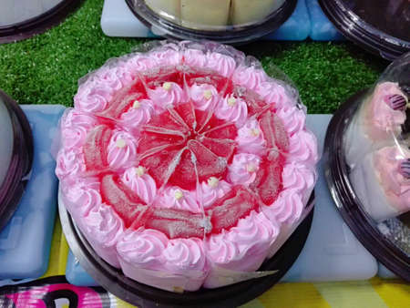 A photo of colorful cream strawberry cake decorated with  topping on sale at streed food market of thailand, close up 版權商用圖片