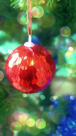 Chirstmas and New year concept: A photo of red ball hanging on a Christmas tree, with bokeh, close up Stok Fotoğraf