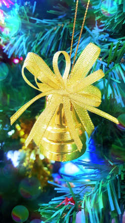 Chirstmas and New year concept: A photo of golden belll hanging on a Christmas tree, with bokeh, close up Stok Fotoğraf