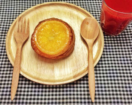 orange tart: Orange tart on wooden plate with tomato juice