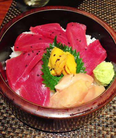 uni: Tuna sashimi with uni on rice in wooden bowl