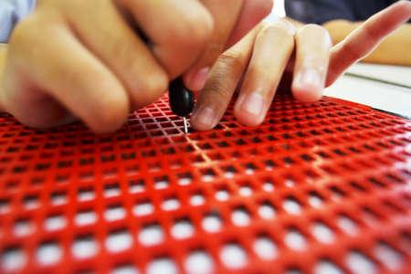 盲児の点字を書く