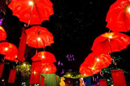 Red umbrella in the night sky with colorful light photo