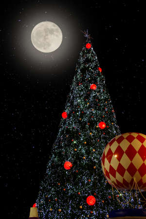 christmas tree in the night sky with full moon photo