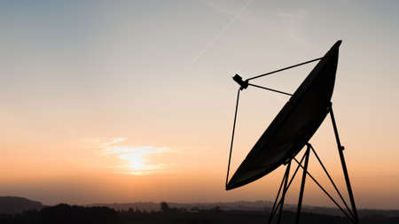 Silhouette of satellite dish in sunset sky photo