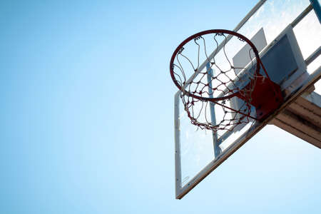 Basketball hoop in outdoor basketball field with blue sky