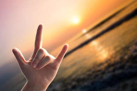 show of hands: Mostra le mani, Segno di amore sulla spiaggia di sfocatura mare con il tramonto Archivio Fotografico