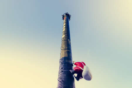 Statue of santa is climbing the chimney