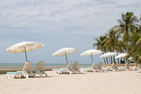 Chair and white umbrella on the beautiful beach with coconut trees in the background