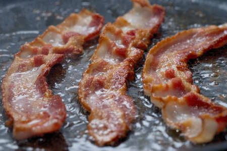 CLOSE UP IMAGE OF BACON BEING FRIED IN PAN - DELICIOUS BUT UNHEALTHY Reklamní fotografie