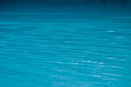 Surface of water in blue swimming pool.