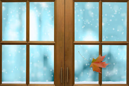 Wooden window frame with outside view of snow and nice freezing blue tone bokeh in background.