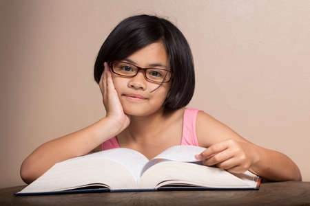 8 10 years: Girl wearing glasses reading at home