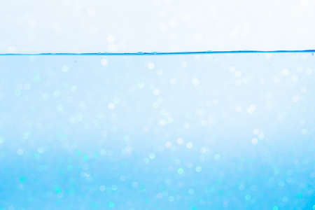 Surface of the blue water waves splash on a white background