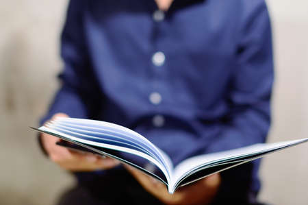 A businessman in a blue shirt Viewing report in notebook