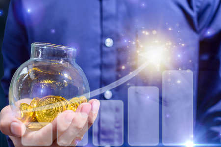 Concept of a businessman saving money in a glass jar And graph showing business growth