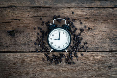 A clock and coffee beans on the desk top view