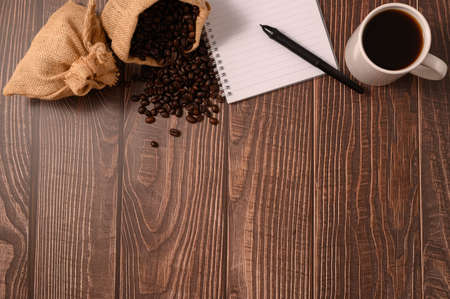 Coffee and a notebook are at your desk. Imagens