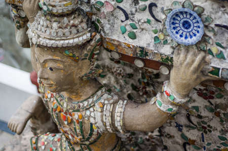 wat pho: Giant, Titan Statue  at Wat Arun  in Thailand  Wat Arun or  Temple of the Dawn  is a Buddhist temple in the Bangkok Thailand  Stock Photo