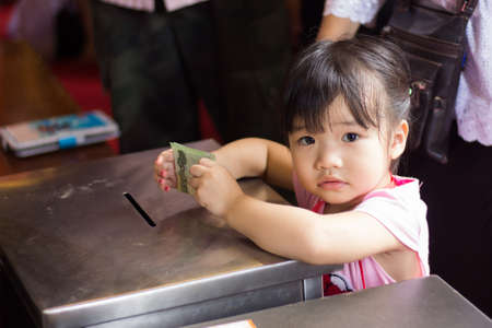 donates: BANGKOK, THAILAND - October 3   Thai Buddhist baby girl donates banknote for Charity on October 3, 2013  Editorial
