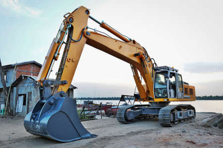 earthmover: excavator is parking beside the Yangon river, to transport construction site, Myanmar Stock Photo