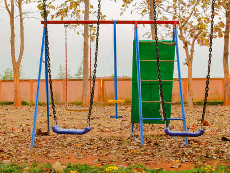 swing set: The colorful swing set in the garden for children to play.
