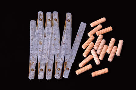 dowel: Wooden dowel pins and folding meter on black background