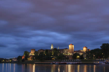 Poland, Krakow, Wawel Royal Castle Lit-up, spring, evening, seen from the south, lights af a passing river-boat, overcast sky