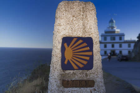 kilometer: Spain, Galicia, Fisterra, milestone, kilometer zero of Camino de Santiago, lighthouse in the background Stock Photo