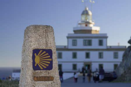 Spain, Galicia, Fisterra, milestone, kilometer zero of Camino de Santiago, lighthouse in the background photo