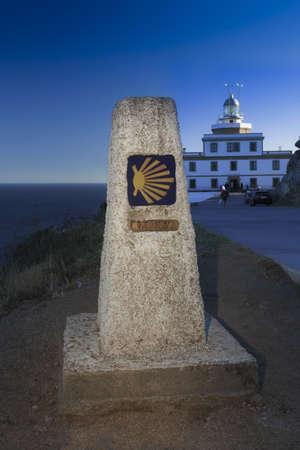 chilometro: Spagna, Galizia, Fisterra, pietra miliare, chilometro zero del Camino de Santiago, il faro sullo sfondo Archivio Fotografico