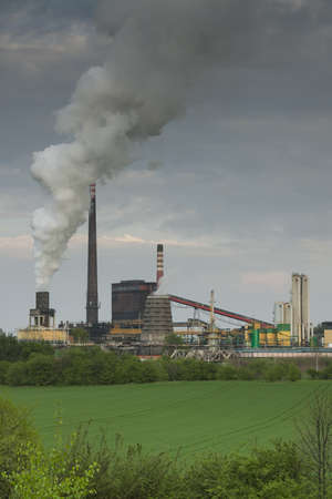 Poland, Zabrze, Biskupice coking plant seen over green field, spring Stock Photo