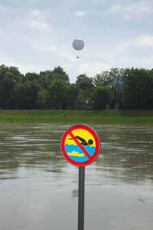 no swimming: Poland, Kraków, flooded VistulaWisła river embankments, no swimming sign over the water, sightseeing baloon in the background