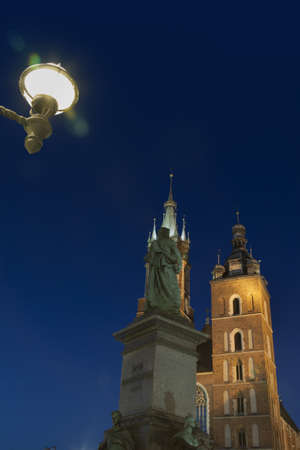 mickiewicz: Poland, Krakow, market square, Mickiewicz monument in the foreground, st Mary (Mariacki) church towers background, illuminated, dusk