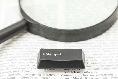 gutenberg: Enter Computer Key on a magnifying glass placed on a book page