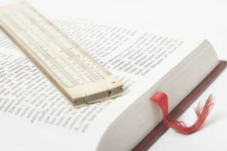 technology symbols metaphors: Vintage slide rule placed on a book page, red bookmark visible Stock Photo