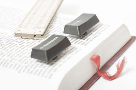Enter and Backspace Computer Keys and a vintage slide rule placed on a book page, red bookmark visible