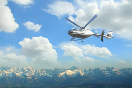 airborn: Silver helicopter in flight over a panoramic view of Tatra mountains in Poland and Slovakia Stock Photo