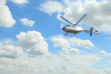 airborn: Silver helicopter in mid-air against overcast sky, white clouds in the background