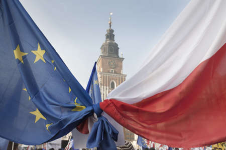 tied together: Polish and EU Flags Tied Together foreground, Krakow Town Hall Tower in the background, clear sky Stock Photo