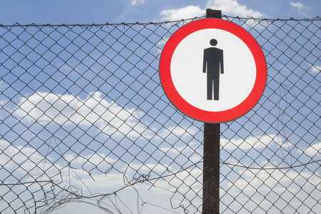 trespasser: No entry sign on a incomplete net fence, blue sky in the background Stock Photo