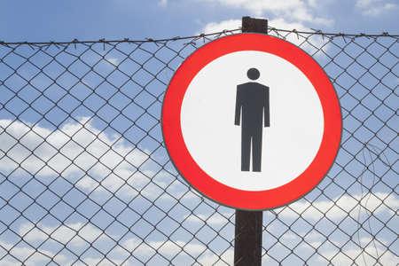 prohibido el paso: Ninguna señal de entrada en una valla de red, cielo azul en el fondo