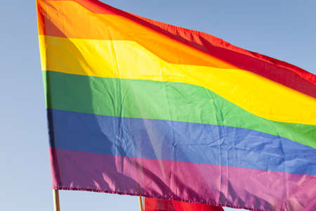 Gay Pride Flag against clear sky, sunlit Stock Photo
