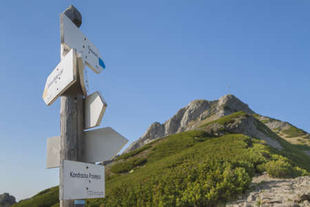 Poland, Tatra mountains, Signpost at Kondracka Prze??cz, overcast sky, Giewont peak in the background Stock Photo
