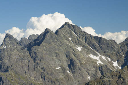 tatra: PolandSlovakia peaks of Tatra mountains, afternoon light, white cloud in the background Stock Photo