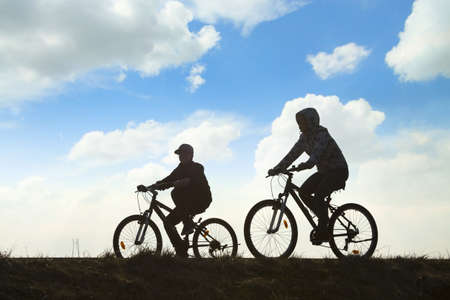 Two cyclists in motion against overcast sky Stock Photo