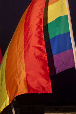 Gay pride flag flying, black background